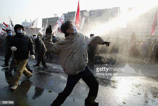 South Korean farmers hurl rocks at riot police during an antigovernment rally against the controversial bill on the free trade agreement with Chile...
