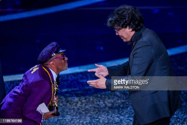 """South Korean film director Bong Joon Ho accepts the award for Best Director for """"Parasite"""" from US director Spike Lee during the 92nd Oscars at the..."""