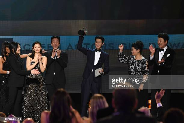 South Korean film director Bong Joon Ho and the cast of Parasite accept the award for Outstanding Performance by a Cast in a Motion Picture during...
