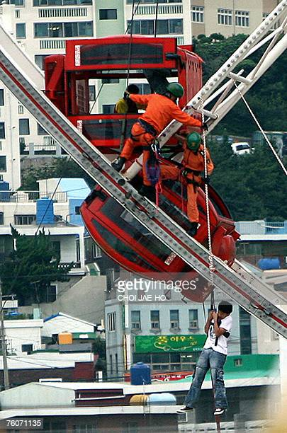 South Korean firefighters rescue students from the car of a ferris wheel at the World Carnival Busan on 13 August 2007. They said a Ferris wheel at...
