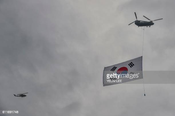A South Korean flag is dispolayed beneath a military helicopter during a commemoration event marking Armed Forces Day at the Gyeryongdae military...