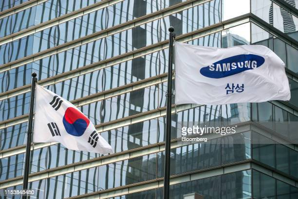 South Korean flag, left, and Samsung Electronics Co. Flag fly outside the company's headquarters in Seoul, South Korea, on Friday, July 5, 2019....