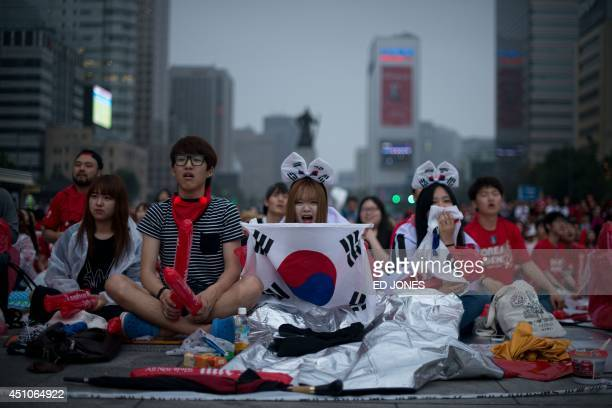 South Korean football fans react as their team loses to Algeria in the 2014 World Cup in Brazil as they watch the match on giant screens in central...