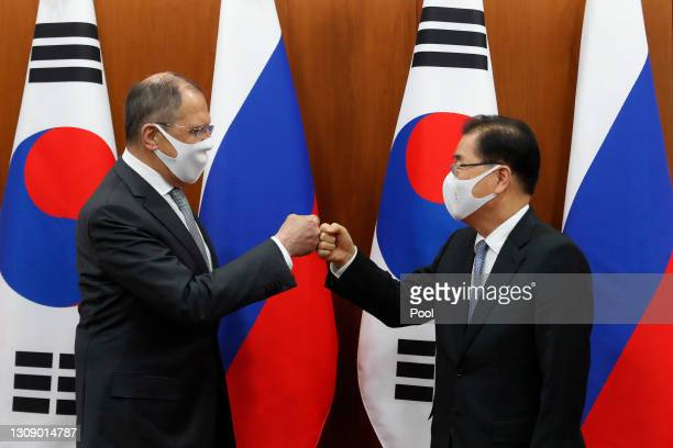 South Korean Foreign Minister Chung Eui-yong bumps elbows with Russian Foreign Minister Sergei Lavrov after a joint announcement at the Foreign...