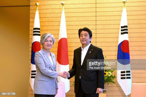 South Korean Foreign Minister Kang Kyungwha and Japanese Prime Minister Shinzo Abe shake hands prior to their meeting on the sidelines of the USSouth...