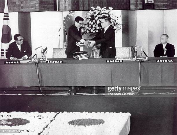 South Korean Foreign Minister Yi Dongwon and Japanese Foreign Minister Etsusaburo Shiina exchange the signed documents while South Korean ambassador...
