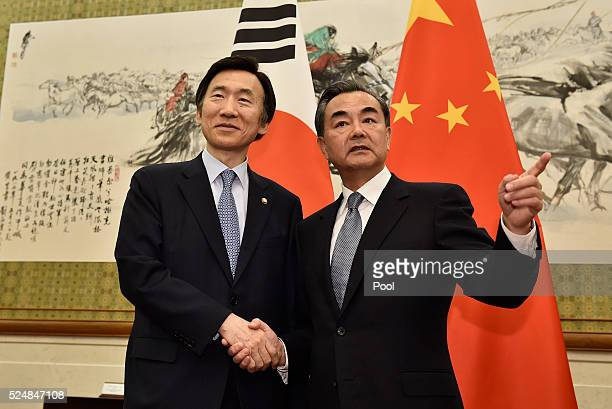 South Korean Foreign Minister Yun Byung-Se shakes hands with Chinese Foreign Minister Wang Yi before a meeting at the Diaoyutai State Guesthouse on...
