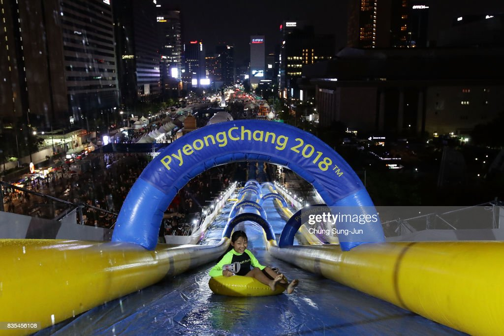 A South Korean girl slides down on an inflatable ring during the 'Bobsleigh In the City' on August 19, 2017 in Seoul, South Korea. The 22-metre-high 300-metre-long water slider has been set up in the central Seoul to promote upcoming PyeongChang Winter Olympics.