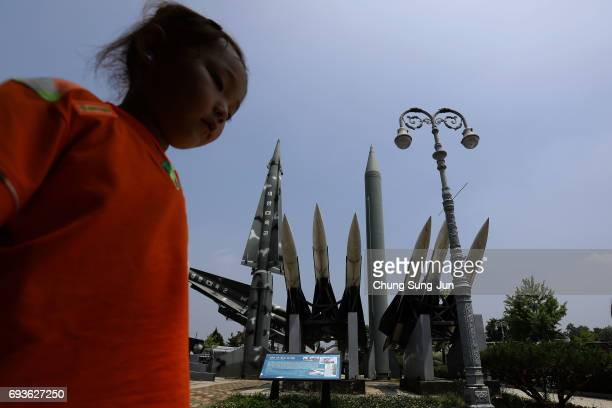 South Korean girl walks past replicas of a North Korean ScudB missile and South Korean Nike missile at the Korean War Memorial in Seoul on June 8...