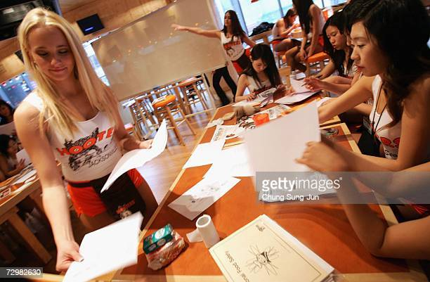 South Korean girls of Hooters undergo training from a US employee at the Hooters restaurant on January 12, 2007 in Seoul, South Korea. The famous US...