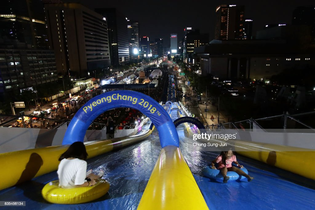 South Korean girls slide down on an inflatable ring during the 'Bobsleigh In the City' on August 19, 2017 in Seoul, South Korea. The 22-metre-high 300-metre-long water slider has been set up in the central Seoul to promote upcoming PyeongChang Winter Olympics.