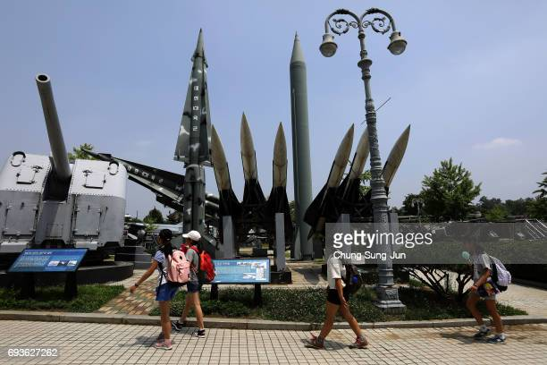 South Korean girls walk past replicas of a North Korean ScudB missile and South Korean Nike missile at the Korean War Memorial in Seoul on June 8...