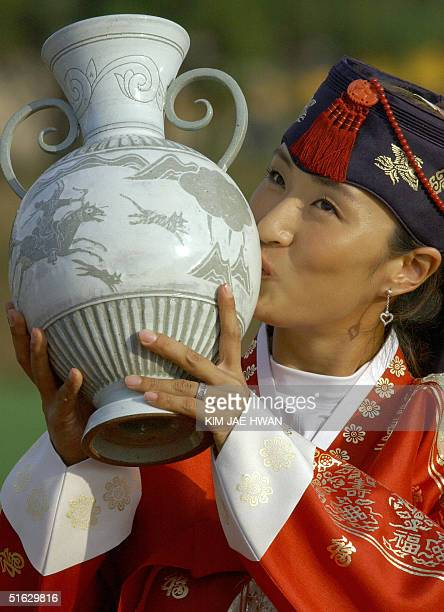 South Korean golfer Grace Park in traditional dress kisses the trophy at the awards ceremony after winning the LPGA Nine Bridges Classic at Jeju...