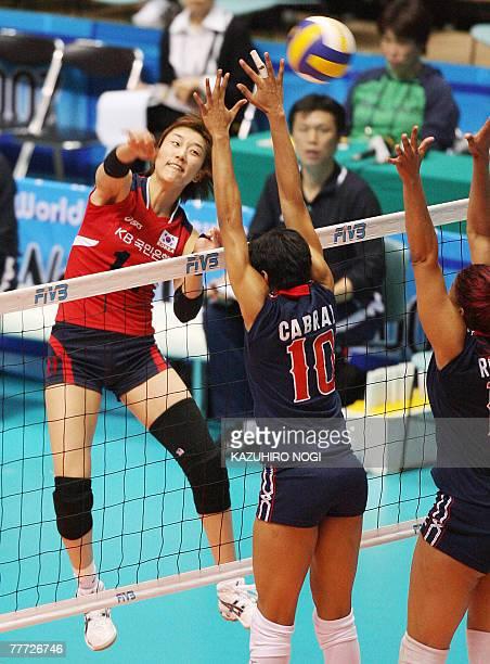 South Korean Han Yoo-Mi spikes the ball over Dominican Republic's blockers, Milagros Cabral de la Cruz and Cosiri Rodrigues Andino during their...