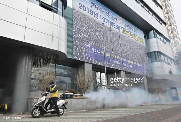 South Korean health official sprays disinfectant in front of the Daegu branch of the Shincheonji Church of Jesus in the southeastern city of Daegu on...