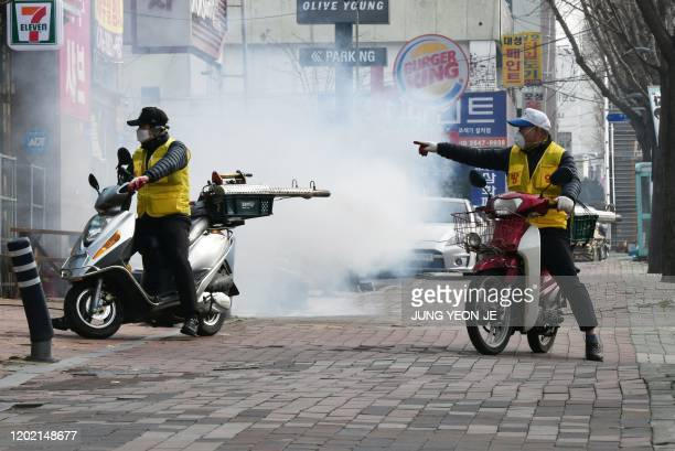 South Korean health officials spray disinfectant in front of the Daegu branch of the Shincheonji Church of Jesus in the southeastern city of Daegu on...