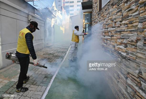South Korean health worker sprays disinfectant as part of preventive measures against the spread of the COVID-19 coronavirus, at a residential area...