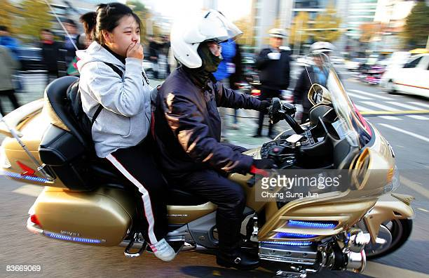 South Korean high school girl arrives at a school by police bike to take the College Scholastic Ability Test on November 13 2008 in Seoul South Korea...