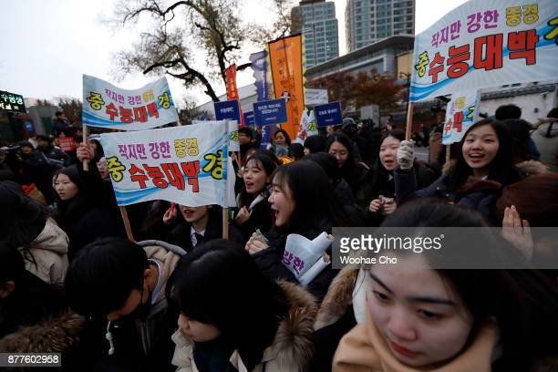 South Korean high school girls cheer on their senior schoolmates taking the College Scholastic Ability Test at a school on November 23 2017 in Seoul...