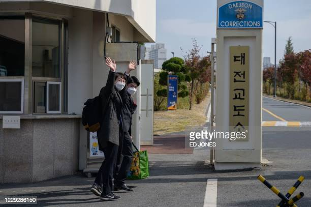 South Korean Jehovah's Witnesses and conscientious objectors to mandatory military service wave to their families as they enter a correctional...
