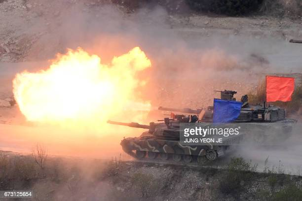 A South Korean K1A2 tank and a US M1A2 tank fire live rounds during a joint live firing drill between South Korea and the US at the Seungjin Fire...