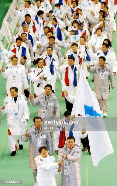 South Korean Kim JaYoun and North Korean Kang HyonSu hold the Unification flag decorated with the image of a united Korean peninsula as they lead a...