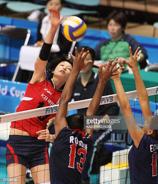 South Korean Kim Yeon-Koung spikes the ball over Dominican Republic's blockers, Cindy Rondon Martinez and Karia Echenique during their second round...