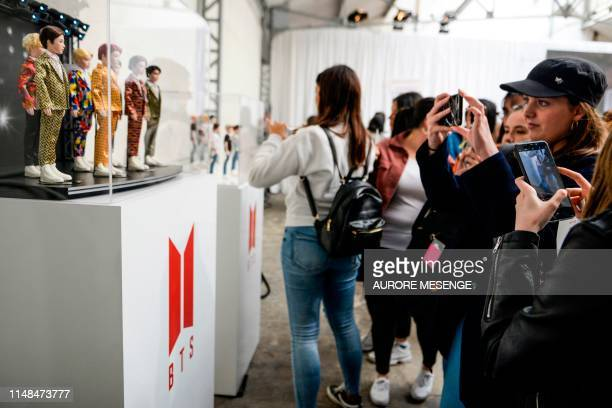 South Korean Kpop boy band BTS' fans take picture of band members' dolls as they came to buy BTS merchandising in a popup store in Paris on June 7...
