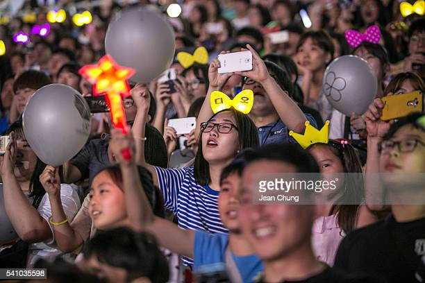 South Korean KPop fans cheer as a KPop band perform on stage on June 18 2016 in Suwon South KoreaThe particular concert was organized by the city...