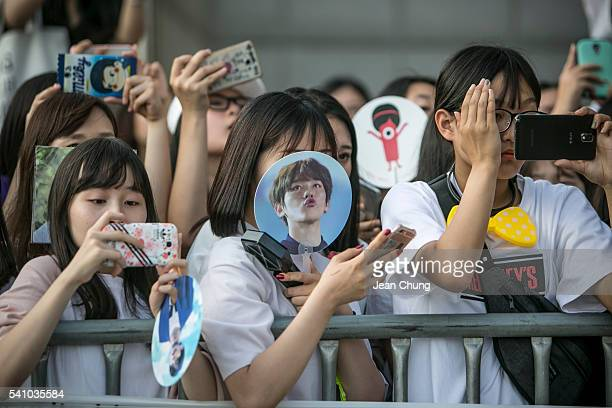 South Korean KPop fans of a boy band called Exo try to cacth a glimpse of boy bands arriving in the parking lot on June 18 2016 in Suwon South...