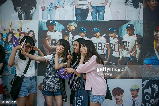 South Korean KPop fans take a snapshot in front of a poster of a boy band called Exo on June 18 2016 in Suwon South KoreaThe particular concert was...