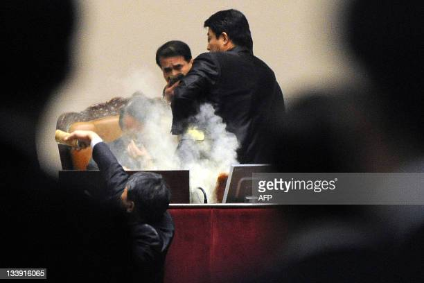 South Korean lawmaker Kim SunDong of the Democratic Labour Party detonates a tear gas canister towards the chairman's seat at the National Assembly...