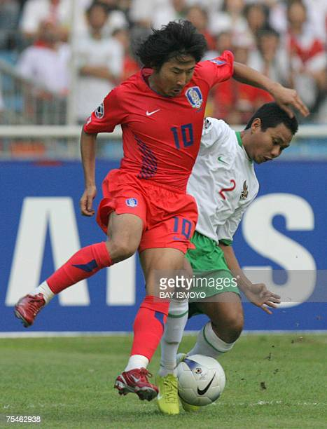 South Korean Lee ChunSoo fights for the ball with Indonesian Muhammad Ridwan during the AFC football cup 2007 match between Indonesia and South Korea...