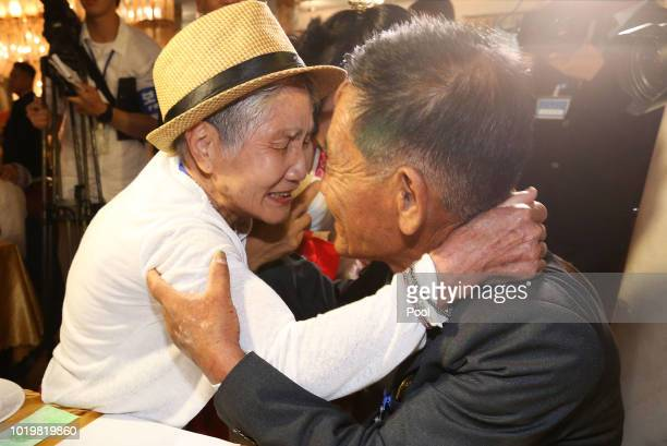 South Korean Choi DongGuy 84 and his North Korean relative Park ChunHwa 58 look photos of family members during a separated family reunion meeting at...