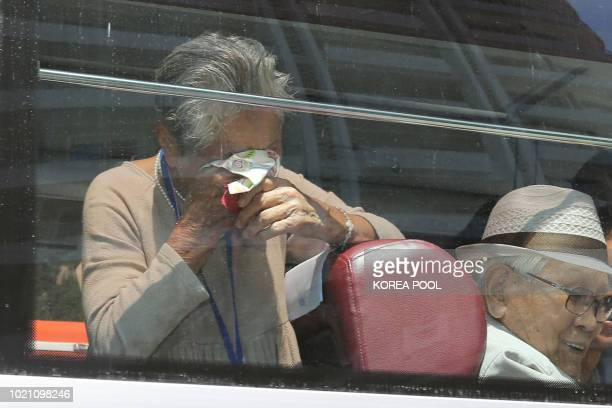 South Korean Lee Keum-seom reacts as she bids farewell through the window to her North Korean son Ri Sang Chol after a three-day family reunion event...