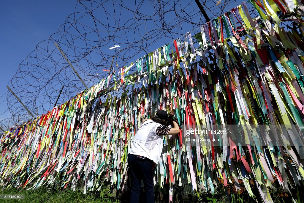A South Korean looks over a ribbon wishing for reunification of the two Koreas on the wire fence at the Imjingak Pavilion, near the demilitarized zone of Panmunjom on September 15, 2017 in Paju, South Korea. North Korea launched a ballistic missile over Japan just days after the U.N. Security Council adopted new sanctions against the regime over its sixth nuclear test on Sept. 3.