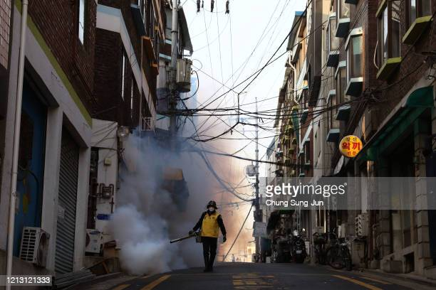 South Korean man disinfects an alley to prevent the coronavirus spread on March 18 2020 in Seoul South Korea According to the Korea Center for...