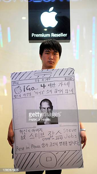 A South Korean man holds a banner paying tribute to Apple cofounder Steve Jobs in front of Apple shop in Seoul on October 6 2011 The world on October...