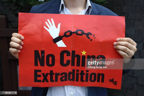 South Korean man holds a placard during a rally to support Hong Kong's protest over extradition law in front of Chinese embassy on June 17, 2019 in...