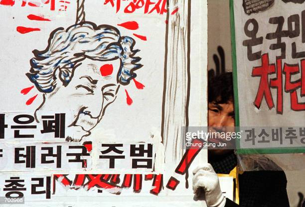South Korean man holds a placard with a drawing of Japanese Prime Minister Junichiro Koizumi during a rally to express anger over Japans 191045...