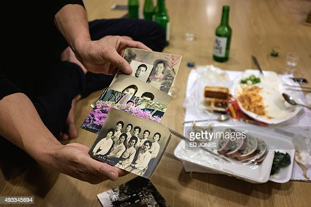A South Korean man holds photos of his North Korean cousins the night before departing for North Korea for a family reunion at a hotel used as a...