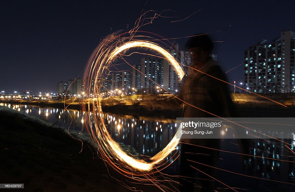 A South Korean man spins a fire can during 'Jwibulnoli' a South Korean folk game at Han River on February 23, 2012 in Seoul, South Korea. The event is part of a 'Daeboreum', a Korean holiday that celebrates the first full moon of the lunar new year.