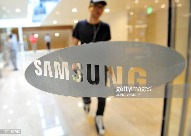A South Korean man walks past a Samsung Electronics logo displayed at the company's main building in Seoul on July 26 2013 Samsung Electronics the...
