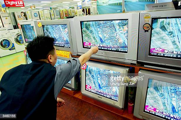South Korean man watches a satellite photo of the train explosion in North Korea on televisions at an electronic department store on April 23 2004 in...