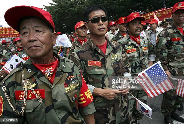 South Korean Marine veteran's hold American flags during a protest and the 56th anniversary of military operations to recover the capital from...