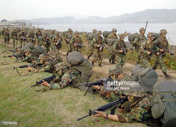 South Korean Marines advance after landing on the beach during a landing drill at Ganghwa 19 October 2006 While visiting Seoul 19 October US...