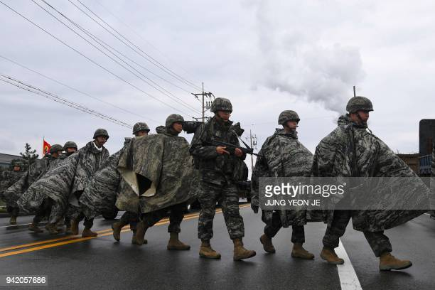 South Korean Marines cross a road after arriving at a port during a joint military exercise in Pohang on April 5 after a combined amphibious landing...