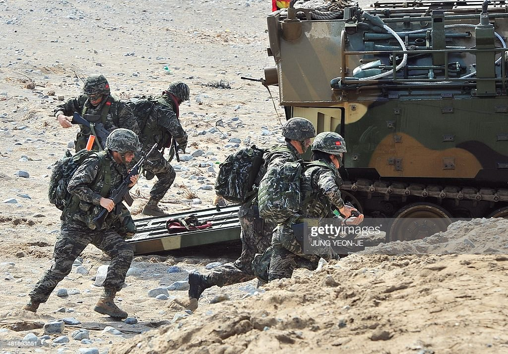South Korean Marines exit an amphibious assault vehicle during a joint landing operation by US and South Korean Marines in Pohang, 270 kms southeast of Seoul, on March 31, 2014. Meanwhile, the two Koreas traded hundreds of rounds of live artillery fire across their disputed maritime border, forcing South Korean islanders to take shelter a day after the North drove up tensions by threatening a new nuclear test.