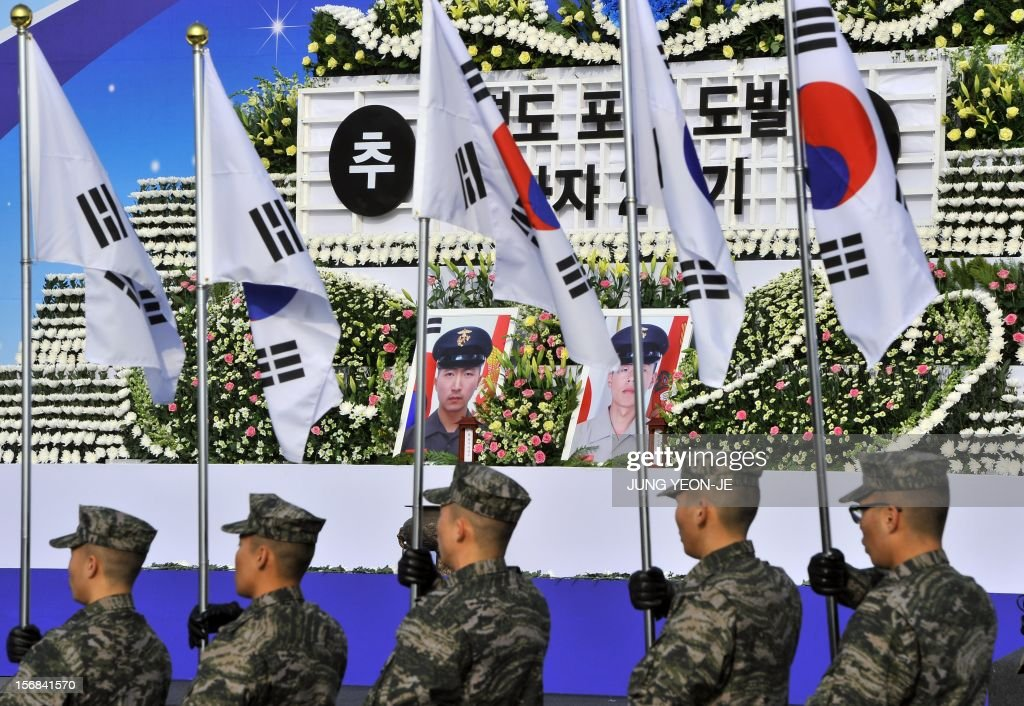 South Korean marines hold national flags in front of a memorial altar for their fallen comrades killed by North Korea's 2010 attack during a ceremony to commemorate the second anniversary of North Korea's shelling of Yeonpyeong Island at the War Memorial in Seoul on November 23, 2012. The November 23, 2010 attack on Yeonpyeong island killed two South Korean marines and two civilians in one of the most serious border incidents since the 1950-1953 Korean War.