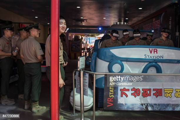 South Korean marines ride a virtual reality machine at an amusement arcade in Incheon following a ceremony marking the '67th anniversary of the...